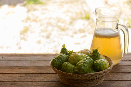 noni: Noni fruit  and noni juice on wooden table.Fruit for health and herb for health.