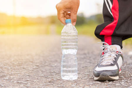 wristbands: Sport man picked water bottle on the floor and background of mountain view.12 Stock Photo