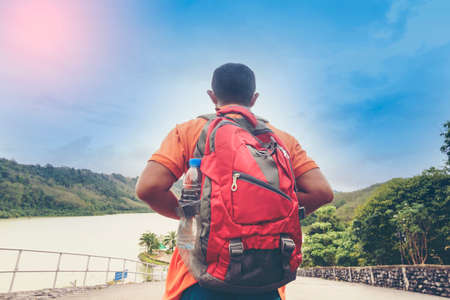 Man Asian backpack looking lake and mountain view. Stock Photo