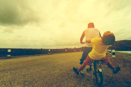 grand son: Father and son are  happy and funny with bike on the road and nature view. Stock Photo
