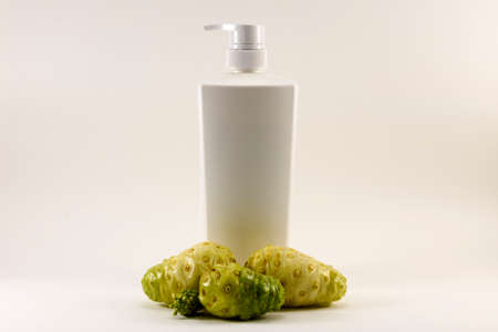 noni: Noni fruit and white bottle isolated.Product from noni. Stock Photo