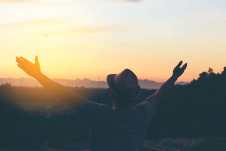 Man hipster show his hand and sunset view.Dark tone