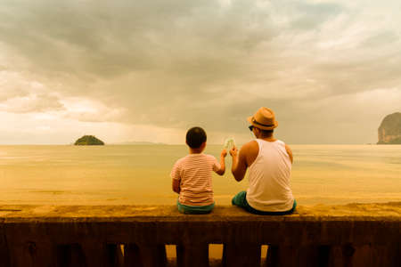 Father and son   holding ice cream Or Family Asian eating ice cream on the beach in the evening. Stock Photo