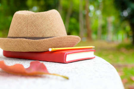 Concept holiday,Notebook and pencil with hat on white table in public park. Stock Photo