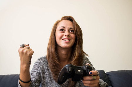 challange: girl celebrates her victory in a game while holding the joystick - Caucasian people - people, technology and lifestyle concept