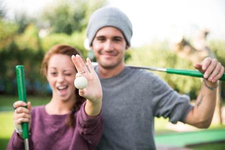 woman golf: young couple laughing and joking in a mini golf course - people, sports, lifestyle concept Stock Photo