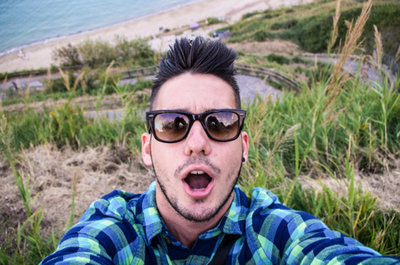Guy take a selfie at the beach - Caucasian people - people, lifestyle and technology concept