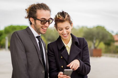 accomplices: Conceptual photo of businessman showing something in the smartphone to His female assistant - Caucasian people - people, business and lifestyle concept