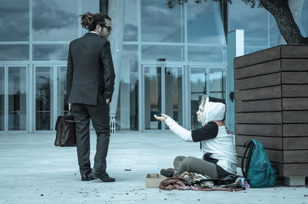 two minds: Business man is disgusted at the sight of a homeless - Caucasian people - business people, poverty and lifestyle concept