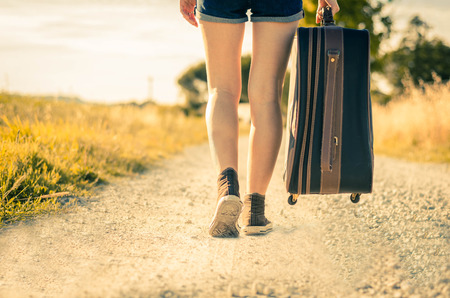 girl walking with her suitcase on vacation - holidays and lifestyle concept Banco de Imagens