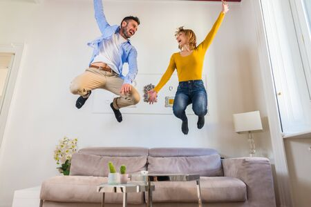 Happy couple in love having fun together jumping on the sofa in the living room at home.