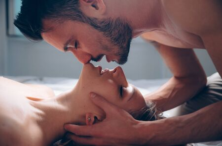 Sensual beautiful couple. Young people kissing at home.