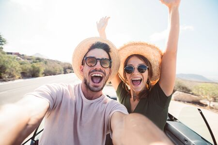 Happy couple in love taking a selfie when road trip in a convertible car