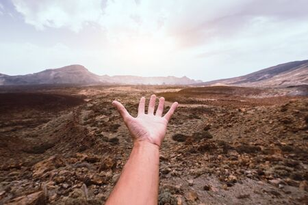 Hand of a man reaching out the beatiful mountain landscape at sunse Stock Photo