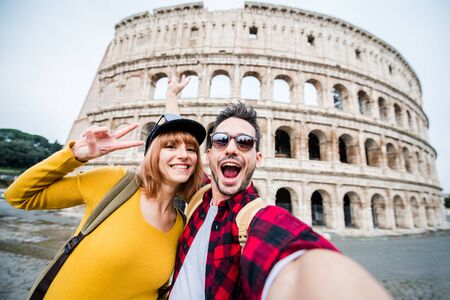 Happy couple of tourist smiling and taking a selfie at the Colosseum in Rome.