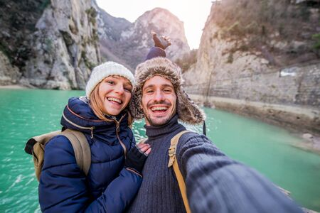 Happy couple of hikers taking a selfie with cell phone at vacation in the mountain at winter