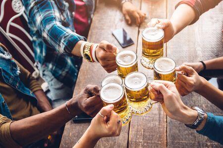Gruppe von Menschen, die ein Bier in der Brauereikneipe genießen und anstoßen - Freundschaftskonzept mit jungen Leuten, die zusammen Spaß haben