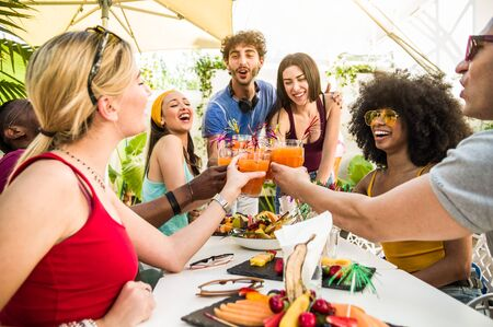 Group of happy multiracial friends having fun drinking and toasting cocktails.