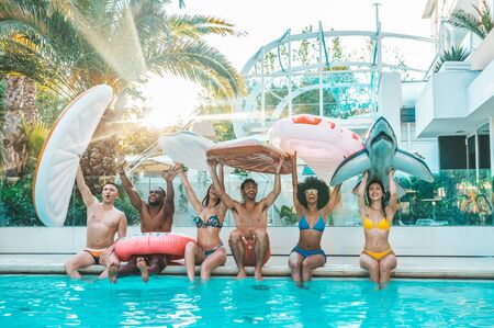 Happy group of friends enjoying swimming pool party at the resort holding inflatables. Young people exclusive holiday with arms up in the hotel.