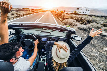 Happy couple driving convertible car on the road - Boyfriend and girlfriend with arms up having fun on a rental auto