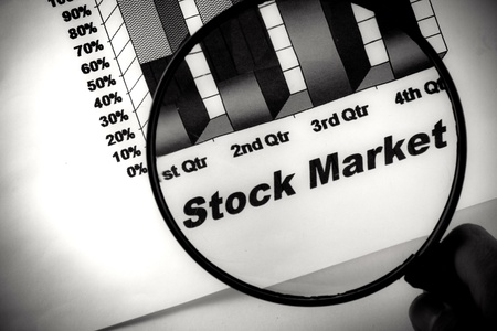 quarterly: black stock market chart under a magnifying glass