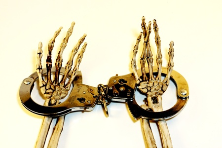 Skeleton hands in handcuffs