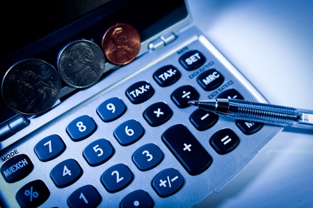 Calculator with stand up coins and a pen Stock Photo