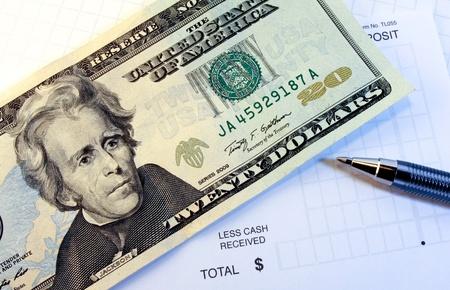 deposit slip: Twenty dollar bill with deposit slip and pen