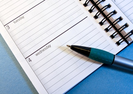 Day planner opened to Wednesday with pointing pen