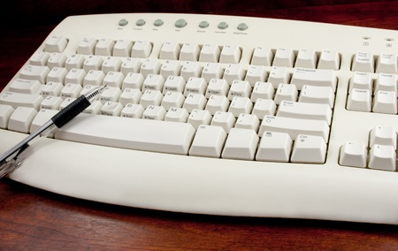 Black pointing pen on top of white keyboard on wooden desk