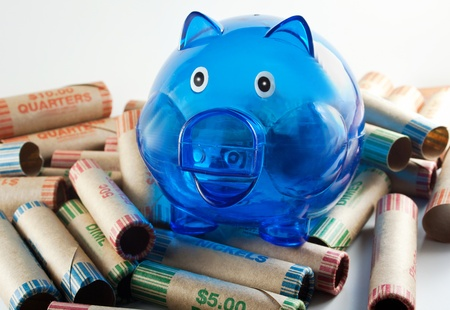 Blue plastic piggy bank sitting on top of coin wrappers