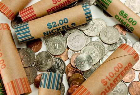 Coins laying with coin wrappers on table