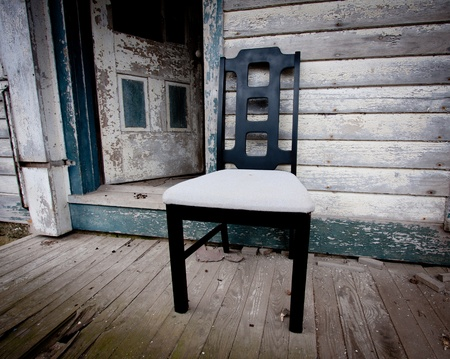 Chair sitting on porch at old abandon house with peeling blue paint Stock Photo