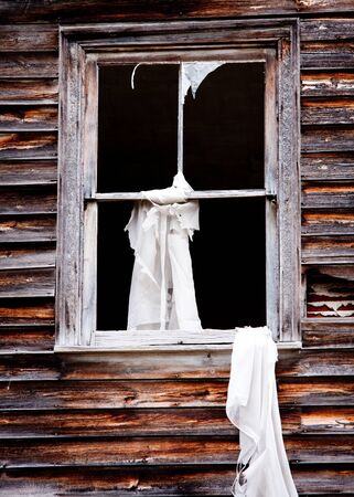A broken window at an abandon house with a torn white curtain hanging out