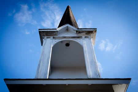 one room school house: Steeple on top of a one room school house in the blue sky with white clouds.