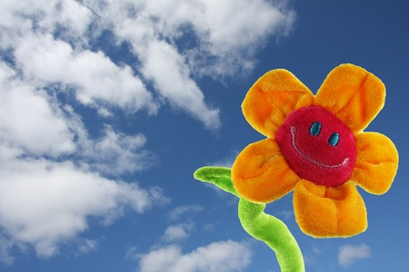 Red and yellow smiling sunflower,with a green stem, in the blue sky with white clouds. Horziontal photo