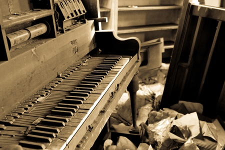 Old dirty piano in a trashed room with garbage on the floor