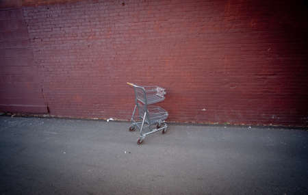 Shopping cart alone against red building in parking lot  photo