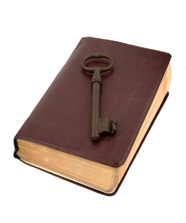 Antique rusty key sitting on top of an old leather book Stock Photo