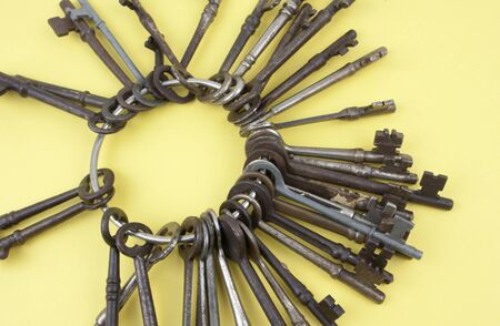 Antique keys together on a keyring over a yellow background Stock Photo
