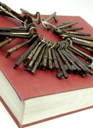 Set of antique keys sitting on top of a red hardcover book