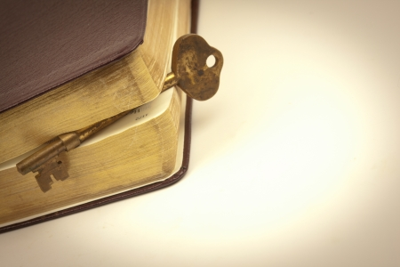 Antique gold key placed inside a book to mark a page photo