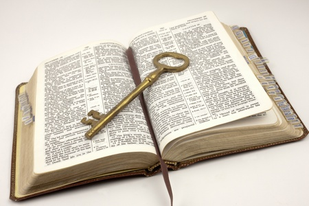Antique gold key sitting on top of an opened bible that is bookmarked