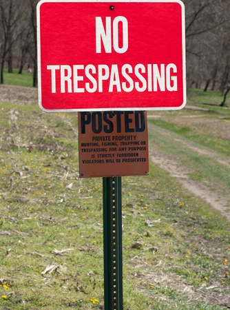 A no trespassing sign in the woods on a green post. A posted sign underneath it