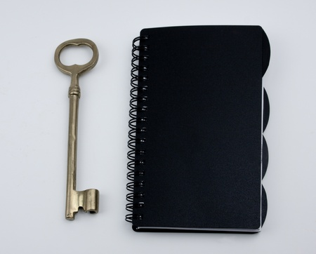 A gold key sitting next to a black day planner. Over white background