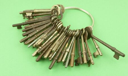 Antique keys on a key ring with a green background
