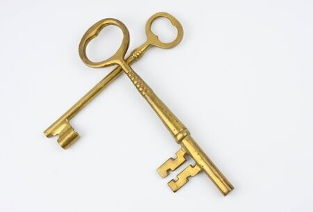 Two gold keys crossing. Over white background Archivio Fotografico