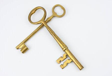 Two gold keys crossing. Over white background Banco de Imagens