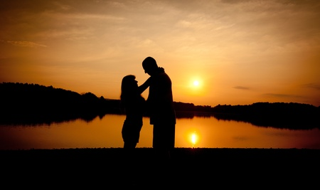 Couple in silhouette sunset with the beach in the backgound photo