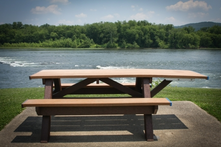 Picnic table sitting in front of a river Stock Photo